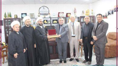 صورة وفد من العتبة الحسينية المقدسة يهدي راية الإمام الحسين عليه السلام إلى كلية الكوت الجامعة .